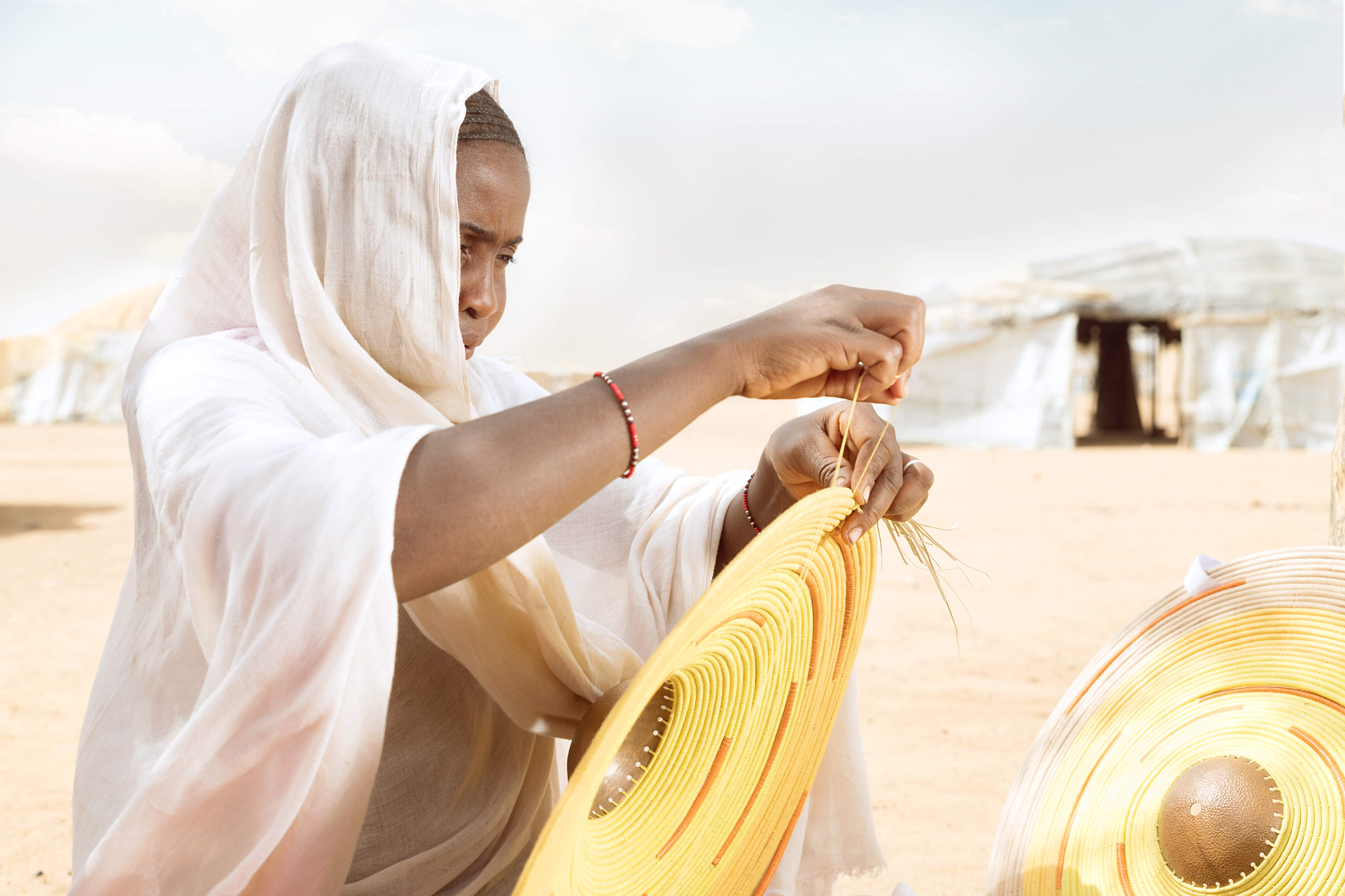 A refugee from Mali weaving a lampshade, using natural grass, leather and bronze.  The work of these Tuareg artisans is supported by the MADE51 partner AAKS. Photo: UNHCR/AAKS