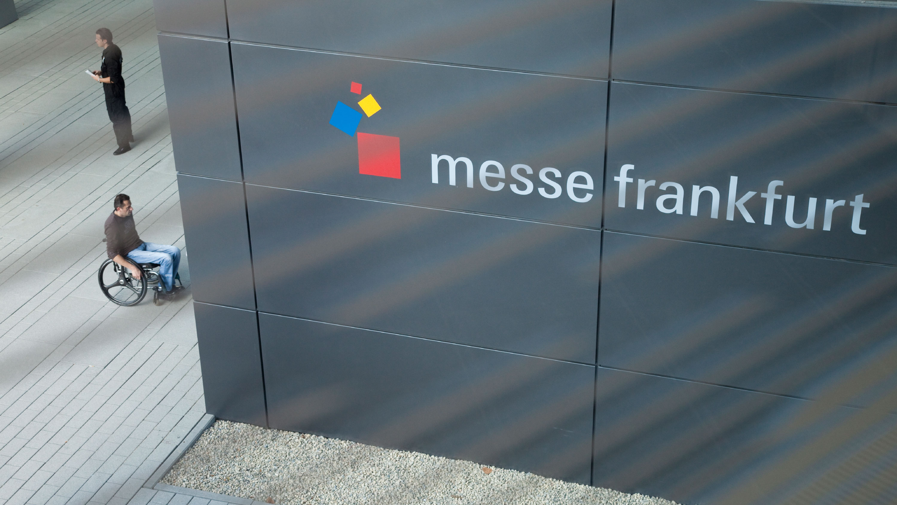 Man in a wheelchair drives to the entrance of Messe Frankfurt